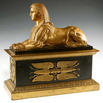 pair of gilt and paginated bronze chenets with sphinx
